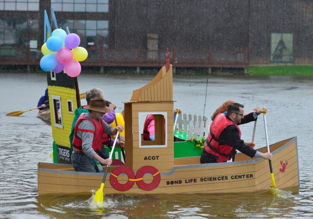 Four people sail a cardboard boat on a lake