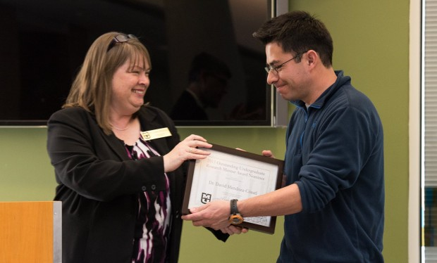 faculty member shakes hands while accepting framed certificate