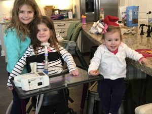 The Sims sisters: Catherine, a SMARD survivor, with older sister Molly and younger sister Caroline. Catherine is standing with the aid of a device.